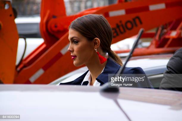 Miss Universe Iris Mittenaere is seen at Spring Studios outside the Lacoste show wearing white shirt blue coat and red tassel drop earrings on...