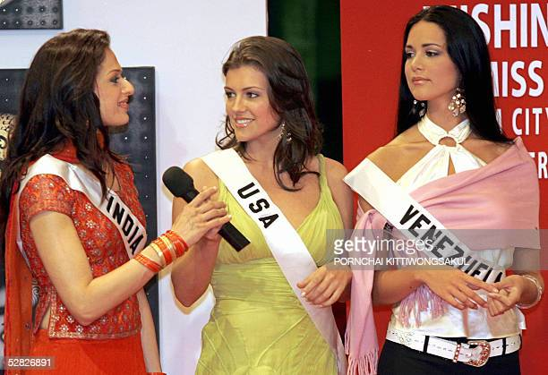 Miss USA Chelsea Cooley passes a microphone to Miss India Amrita Thapar as Miss Venezuela Monica Spear looks on during a Miss universe promotional...