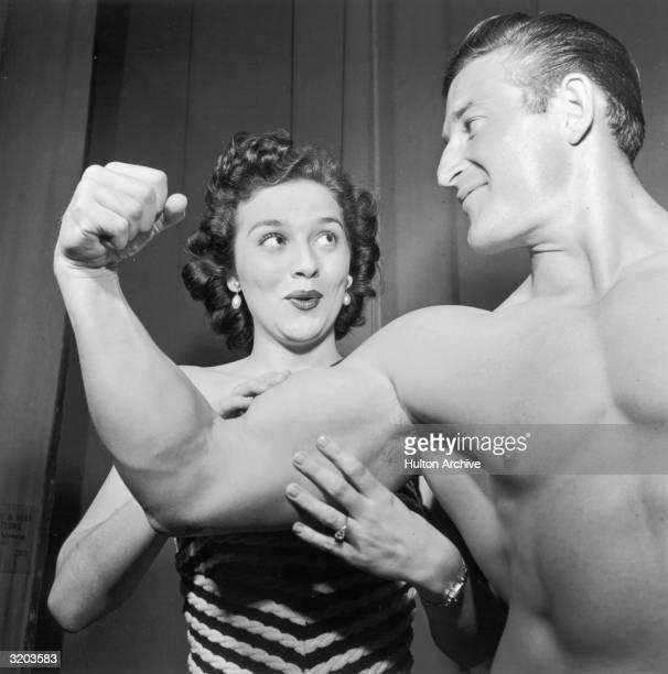 Miss U.S.A. Contestant Jean Wills admires strongman Bob McAine's flexed bicep.