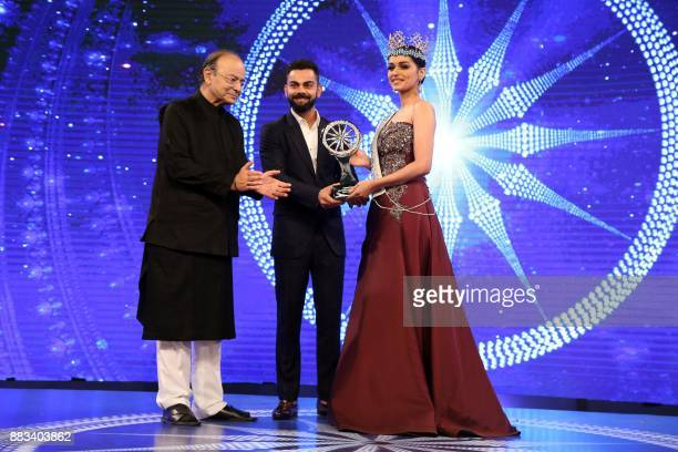 Miss World 2017 Manushi Chhillar and Indian cricketer Virat Kohli hold up the CNNIBN Special Achievement Award during an awards ceremony in New Delhi...