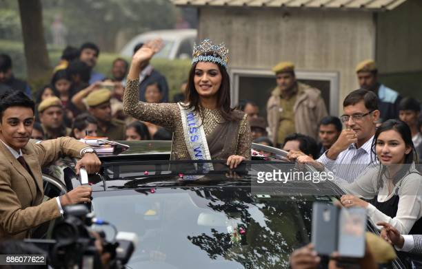 TOPSHOT Miss World 2017 Manushi Chhillar waves as she stands out of the sunroof of a car during a parade in New Delhi on December 3 2017 Indian model...