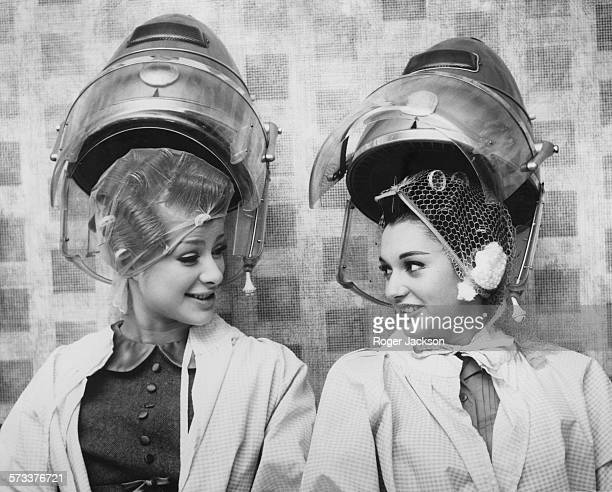Miss World contestants Agneta Malmgren of Sweden and Maria Madronero of Spain under blowdryers at 'La Belle' hair fashion salon on the eve of the...