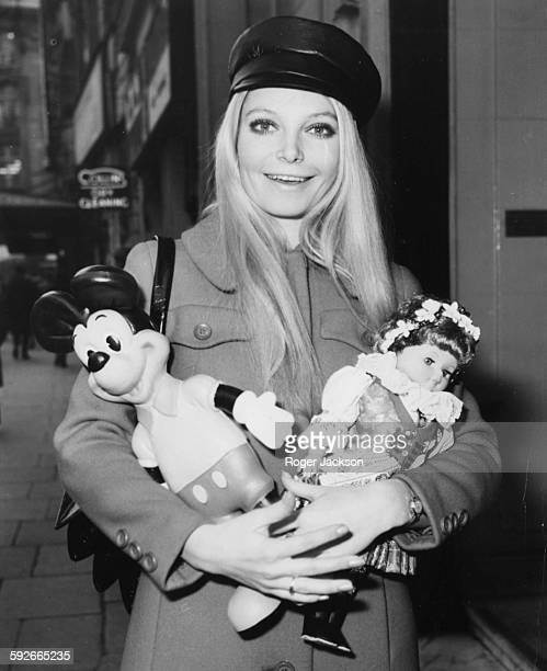 Miss World winner Eva RueberStaier holding a Mickey Mouse doll and a Czech doll as she prepares to return home to Austria following the competition...
