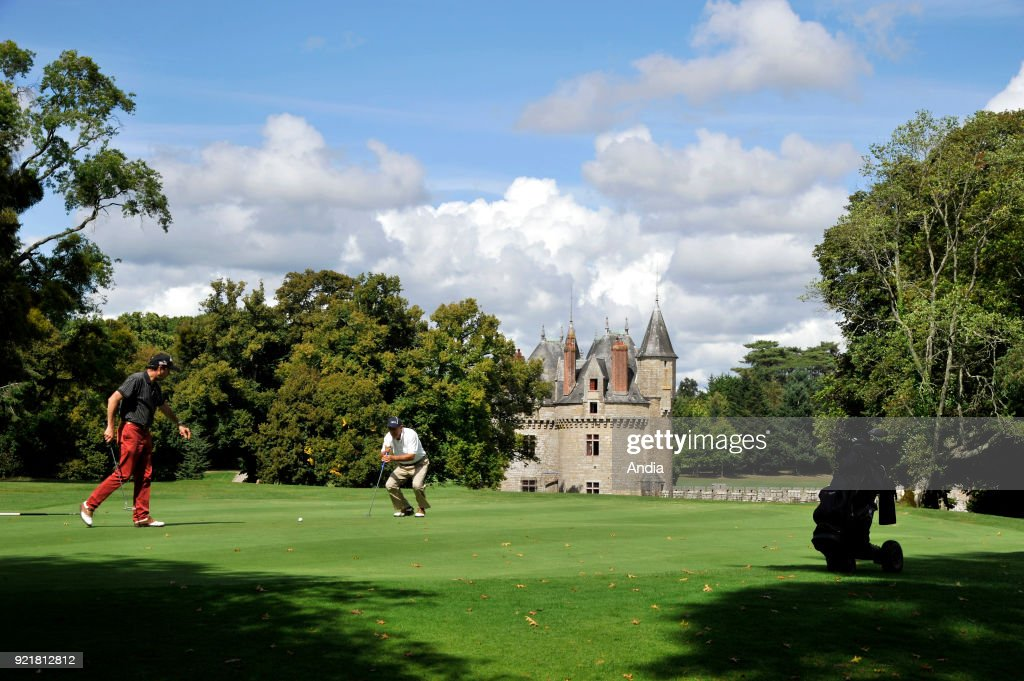 Missilac (north-western France). Golfer on the golf course of at the bottom of the 'Chateau de La Bretesche', a medieval castle built in the XIVth century, rebuilt in the XIXth century, listed as a National Historic Landmark (French 'Monument historique').
