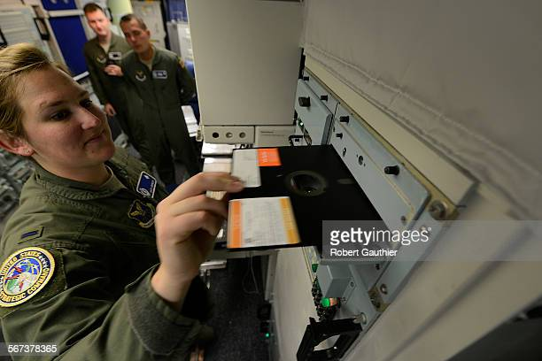 FALLS MONTANA 2014 Missile combat crew member 1st Lt Katie Grimley slides a large floppy disk into a 60's era communication module inside the launch...
