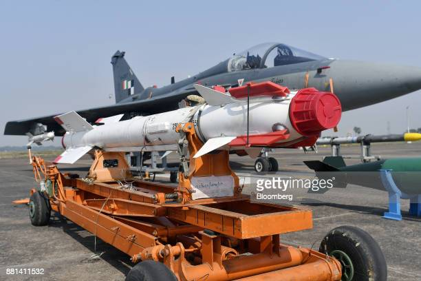 A missile sits on the tarmac in front of an Indian Air Force Tejas fighter jet developed by Hindustan Aeronautics Ltd at the Kalaikunda Air Force...