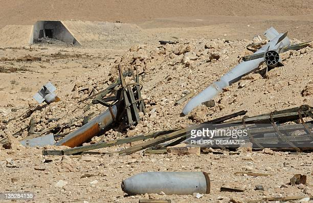 Missiles and shells lie in front of an ammunition storage bunker built in the mountains near the southern Libyan town of Waddan in the oasis of...