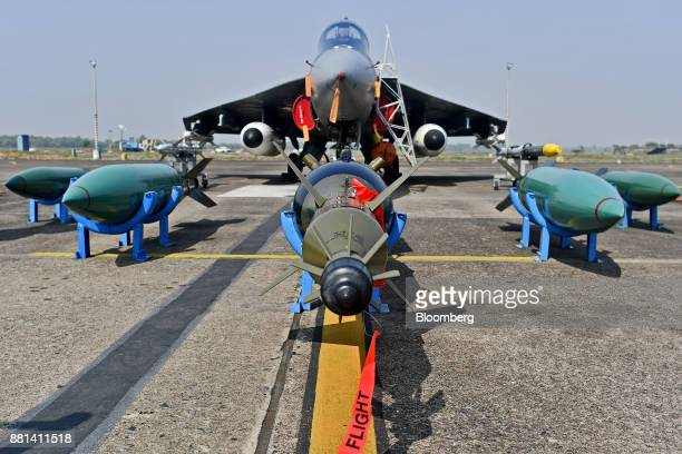 Missiles sit on the tarmac in front of an Indian Air Force Tejas fighter jet developed by Hindustan Aeronautics Ltd at the Kalaikunda Air Force...