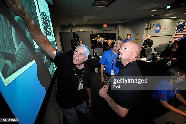 Mission Control team members Eric DeJong and Ed Sedivy look at the first images from NASA's Phoenix Mars Lander arrive after touchdown in a northern...
