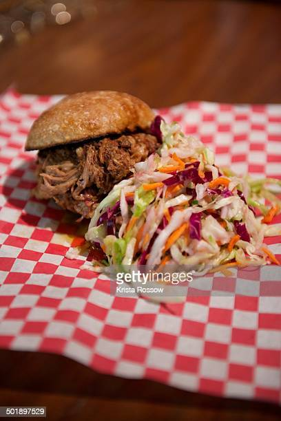A pulled pork sandwich with coleslaw served on red checkered paper.