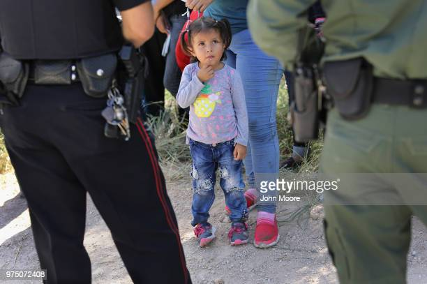 Mission Police Dept officer and a US Border Patrol agent watch over a group of Central American asylum seekers before taking them into custody on...