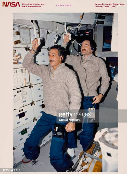 Mission Specialist Jeffrey A Hoffman and Pilot Guy S Gardner holding Development Test Objective 634 trash compactor handles to the ceiling commute to...