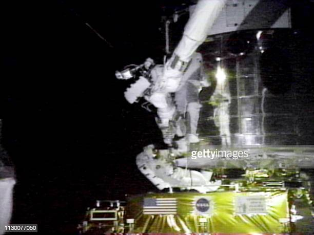 US Mission Specialist John Grunsfeld is reflected on the skin of the Hubble Space Telescope as he rides Discovery's robot arm 22 December while US...