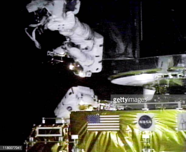 US Mission Specialist John Grunsfeld organizes his tools 22 December as US Payload Specialist Steve Smith prepares to replace another one of the...