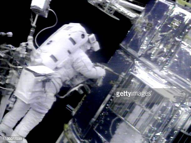 US Mission Specialist John Grunsfeld tightens a screw on one of the Hubble Space Telescope's service panels 22 December as he and US Payload...