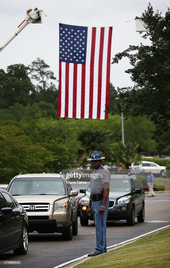 A Mississippi Highway Patrol officer keeps watch beneath an American