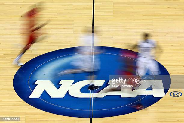 Mississippi Rebels and Xavier Musketeers players run by the logo at mid-court during the second round of the 2015 NCAA Men's Basketball Tournament at...