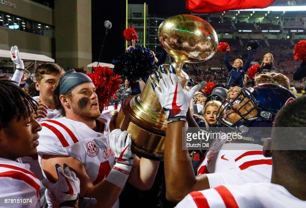 Mississippi Rebels players celebrate by hoisting the Egg Bowl trophy after defeating the Mississippi State Bulldogs 3128 in an NCAA football game at...