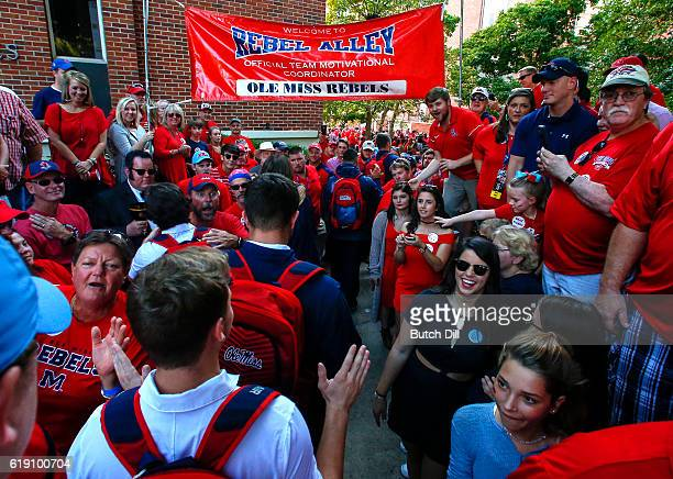 Mississippi Rebels players greet fans as they walk down Walk of Champions in the Grove before an NCAA college football game against the Auburn Tigers...