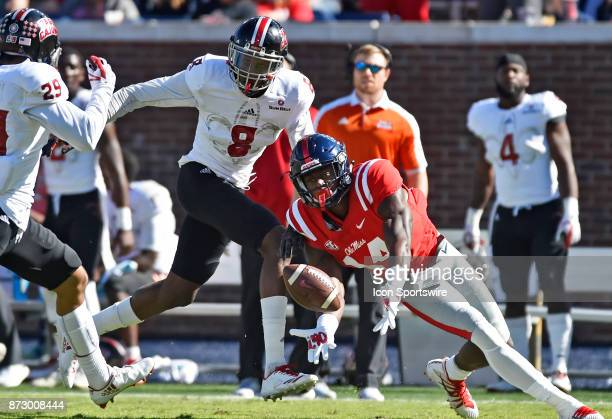 Mississippi Rebels receiver DK Metcalf reaches for the ball between two Louisiana Ragin' Cajun defenders during the first quarter of a college...