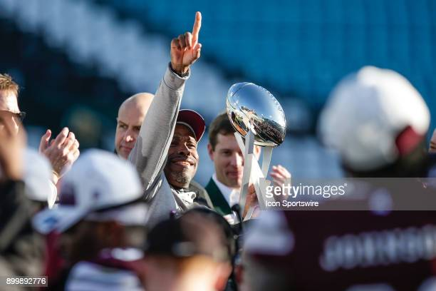 Mississippi State Bulldogs interim head coach Greg Knox celebrates with the game trophy following the game between the Louisville Cardinals and the...