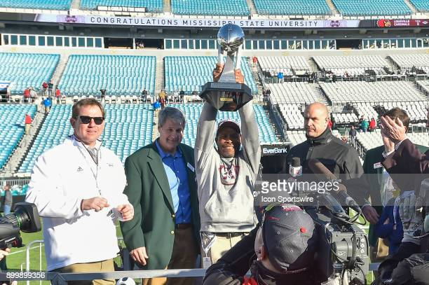 Mississippi State Bulldogs interim head coach Greg Knox holds up the winners' trophy following the TaxSlayer Bowl game between the Louisville...