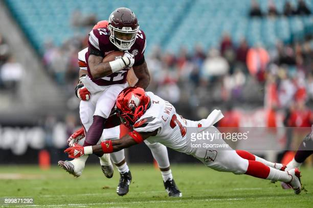 Mississippi State Bulldogs running back Aeris Williams tries to run through the tackle by University of Louisville Cardinals safety Chucky Williams...