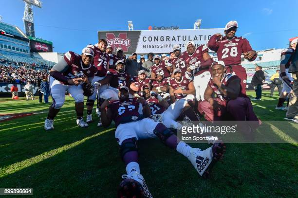 Mississippi State players celebrate and pose for an image after winning the TaxSlayer Bowl game between the Louisville Cardinals and the Mississippi...