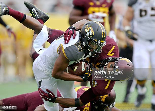 Missouri receiver Bud Sasser is brought down by Minnesota's Demarius Travis during the Buffalo Wild Wings Citrus Bowl at Citrus Bowl Stadium Thursday...