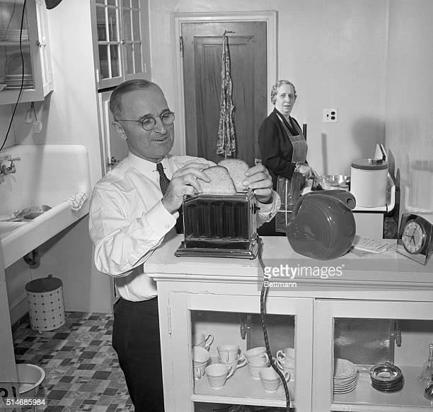 Missouri Senator Harry S Truman helps his wife Bess make breakfast by putting bread in the toaster in their kitchen in Washington DC Truman is...