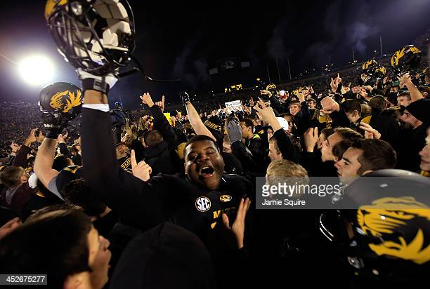 Missouri Tigers players celebrate as fans rush the field after the Tigers defeated the Texas A&M Aggies 28-21 to win the game on November 30, 2013 in...