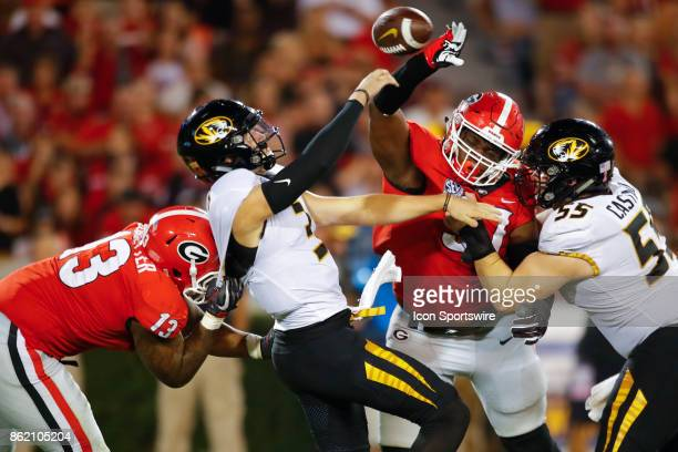 Missouri Tigers quarterback Drew Lock is pressured and hit by Georgia Bulldogs defensive end Jonathan Ledbetter and nose tackle John Atkins in the...