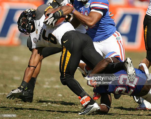 Missouri's Marcus Murphy is pulled down by Florida defensive back Matt Elam during the University of Missouri Tigers at the University of Florida...