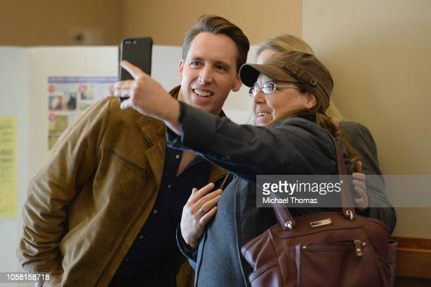 Missouri's Republican US Senate Candidate Josh Hawley and wife Erin Hawley take a selfie photo with a supporter prior to casting their votes on...
