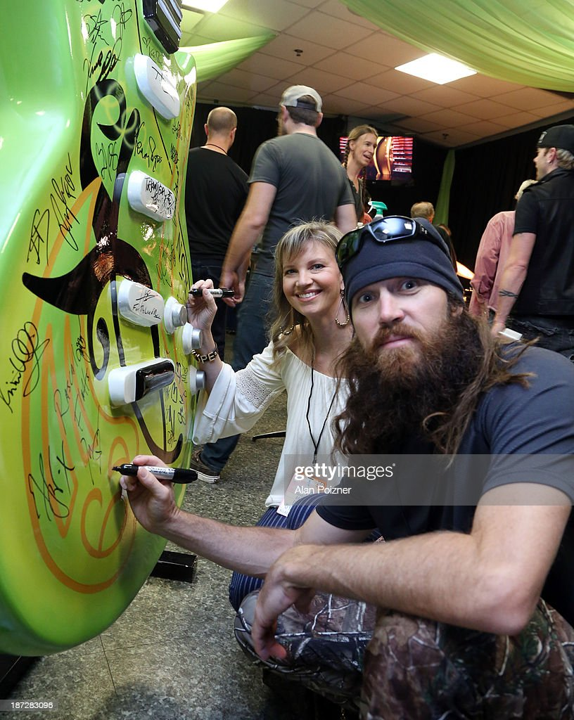 Missy Robertson and Jase Robertson of Duck Dynasty sign a giant Patron tequila guitar backstage at the CMA Awards to benefit the 'Keep the Music Playing' music education on November 3, 2013 in Nashville, Tennessee.