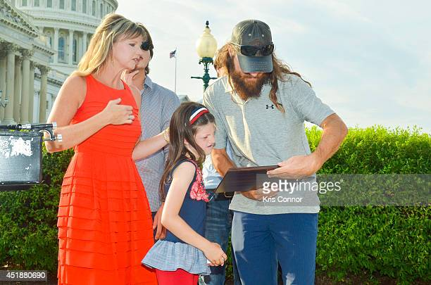 Missy Robertson Mia Robertson and Jase Robertson from 'Duck Dynasty' look over a Certificate of Special Congressional Recognition from Rep Trent...