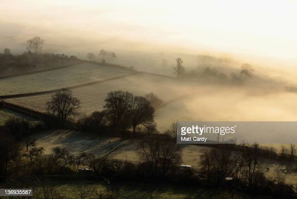 Mist and fog rolls across agricultural fields as the sun rises over the Somerset Levels on January 13 2012 in Glastonbury England After unseasonably...