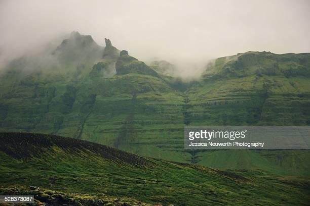 Mist around green mountain peaks in Iceland
