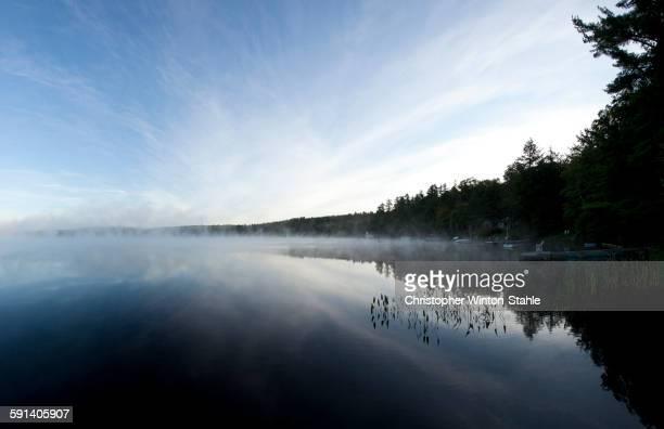Mist clouds over still lake in remote landscape