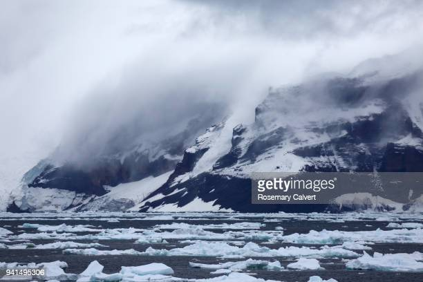 Mist hangs over mountains, Antarctic Sound, Antarctica.
