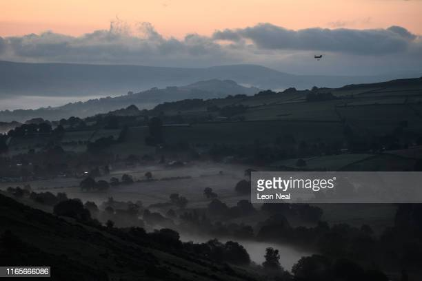 Mist is seen in the valleys before sunrise as a Chinook helicopter prepares to drop sandbags onto the dam wall at Toddbrook reservoir following a...