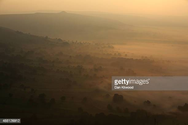 Mist lingers in Hope Valley at sunrise viewed from the top of Mam Tor in the Peak District on September 10 2014 in Castleton United Kingdom Much of...