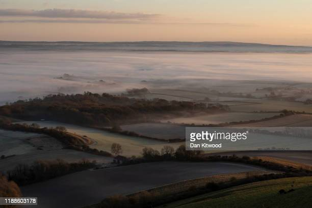Mist lingers in the valley below Firle Beacon in the South Downs on November 19, 2019 in Lewes, England. The UK experienced the coldest night of the...