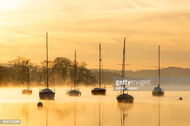 mist over lake windermere in ambleside at dawn, lake district, uk. - ambleside stock photos and pictures