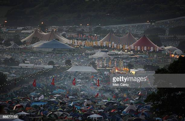 Mist rises over tents as the sun sets as music fans start to arrive at the Glastonbury Festival site at Worthy Farm, Pilton on June 24, 2009 in...