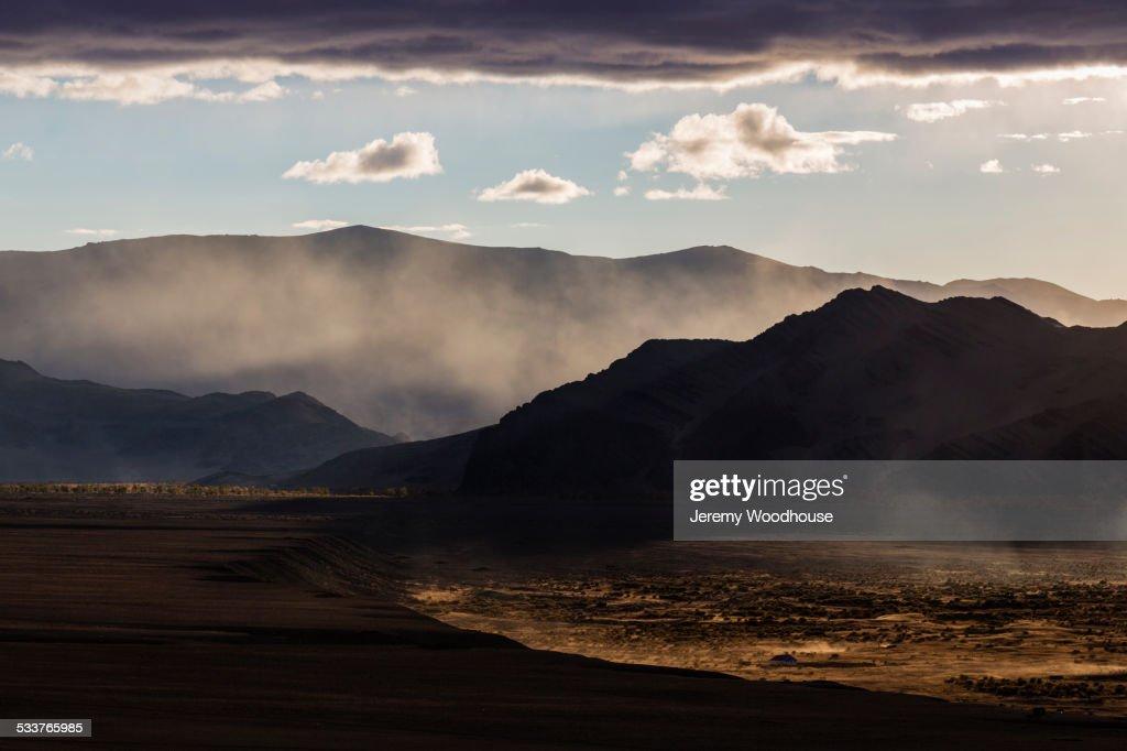 Mist rising from hills in desert landscape : Foto stock
