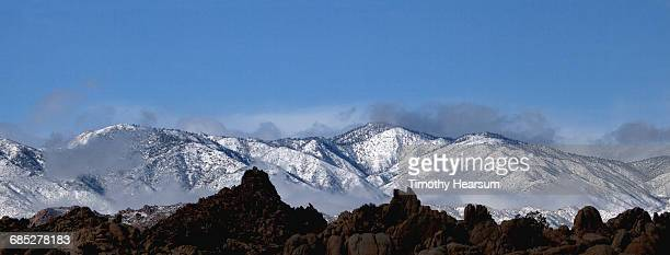 mist rising from snow covered mountains - timothy hearsum imagens e fotografias de stock