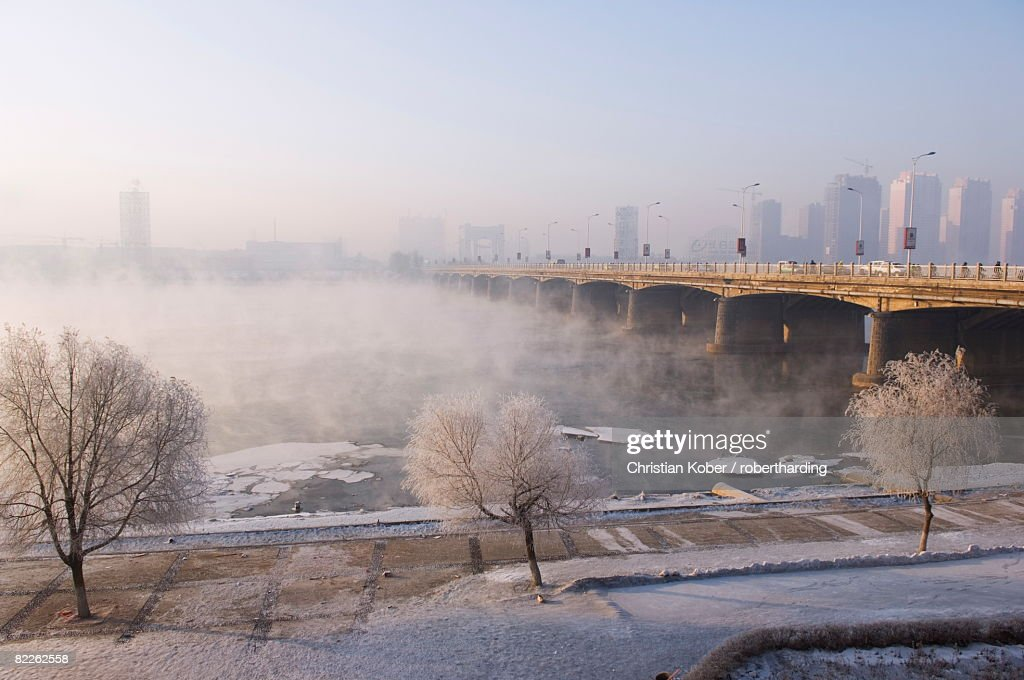 Mist rising off Songhua River and ice covered trees in winter, Jilin City, Jilin Province, Northeast China, China, Asia : Stock Photo