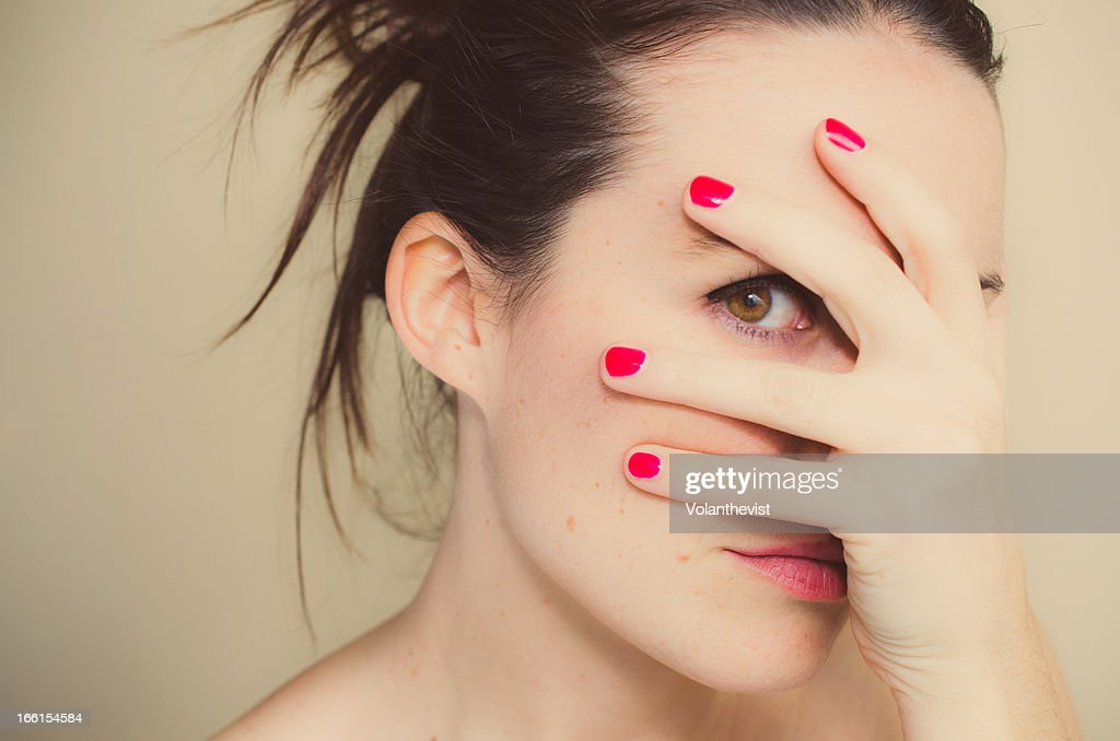 Misterious girl with red nails and hand on face. : Stock Photo