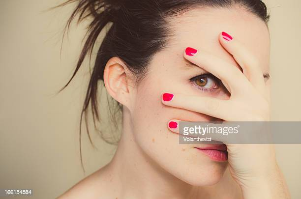 misterious girl with red nails and hand on face. - blame stock pictures, royalty-free photos & images